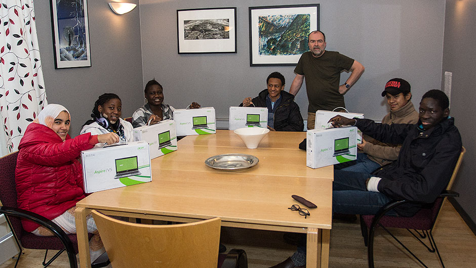 Thanks to our alumni! Here, students receiving laptops